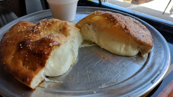 Calzone dripping with cheese